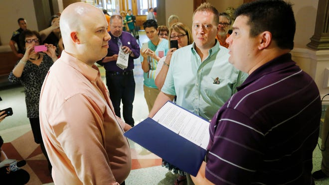 Matt Hicks, right, of American Marriage Ministry, officiates the wedding of Dan Peo, left, and Douglas Taylor on June 26 in the Tippecanoe County Courthouse. The couple were the first in line to obtain their marriage license once Tippecanoe County started issuing licenses. Moments later, they took their marriage vows.
