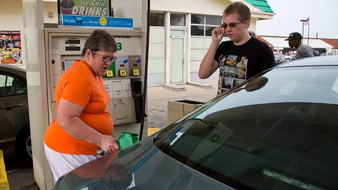 Pam Detamore, a Congress Street United Methodist Church member, fills up Nolan Hoffman's car Thursday during an event called Gas Buy Down at the BP station at Teal Road and South 22nd Street.