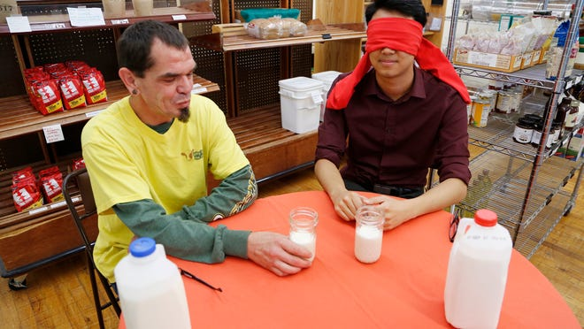 Heath Terhune of Pasture's Delights prepares to serve a blindfolded Journal & Courier Arts and Entertainment reporter Wei-Huan Chen whole milk and raw milk to compare taste.