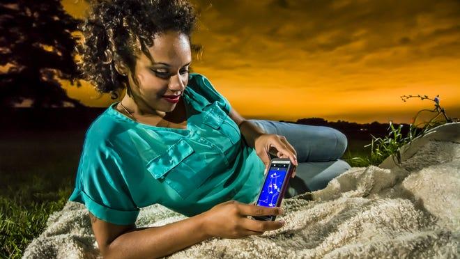 Tashmica Torok uses her Google Sky app to aid in her star gazing Saturday July 28, 2013 in Mason.  KEVIN W. FOWLER PHOTO