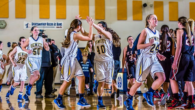 Members of the DeWitt girls basketball team celebrate as they leave the floor after their 47-44 win over St. Johns Friday.