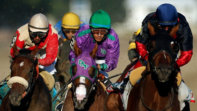 California Chrome, center, is flanked by Wicked Strong, left, and Tonalist, right, as they run down the backstretch during the the Belmont Stakes.