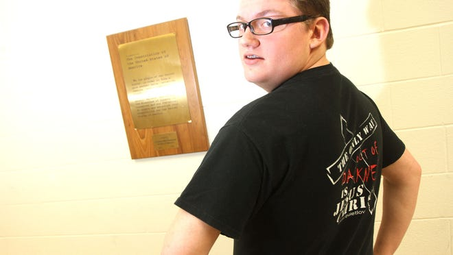 Harding freshman Anthony Miller stands in a hallway where a copy of the U.S. Constitution hangs next to the spot where a plaque listing the Ten Commandments once hung, but was recently taken down by school administrators. Miller, an evangelical Christian, says he has over 100 signatures on a petition to have the plaque, donated to the school in the '50's, returned to the hallway. James Miller/The Marion Star
