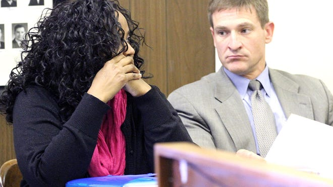Brenda Nwosu keeps her face hidden during a plea hearing in April in Marion County Common Pleas Judge William Finnegan's courtroom.