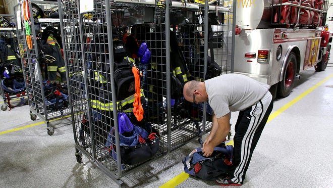 Firefighter Jeff Clark goes through his gear at the station Monday. The Yorktown Fire Department is one of many volunteer departments in Delaware and surrounding counties.