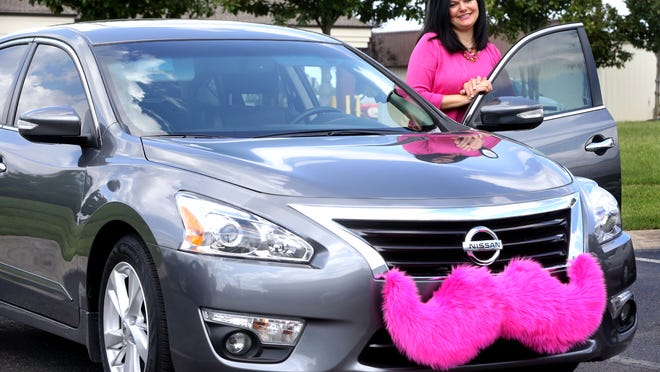 Lisa Stafford, a driver for Lyft, Thursday stands next to her car that she uses for ride-sharing job. Stafford said Lyft has changed her life.