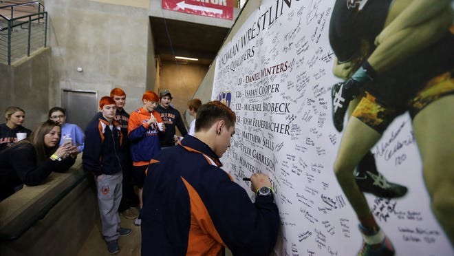 Blackman wrestler Hunter Winters signs a banner remembering his brother, Daniel Winters who was killed in an auto accident earlier in the week, before the start of the TSSAA state wrestling championships Thursday in Franklin. Both Blackman and Siegel are wrestling in memory of former wrestlers this week at the state duals tournament.