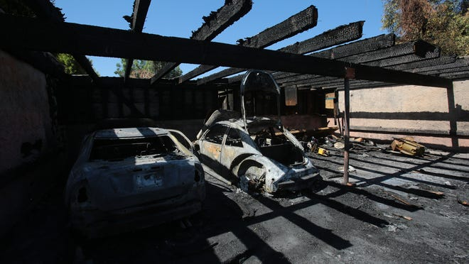 A pair of cars remained Sunday morning amid damage from a fire in a carport area Saturday night at Los Arboles Apartments in Indio.
