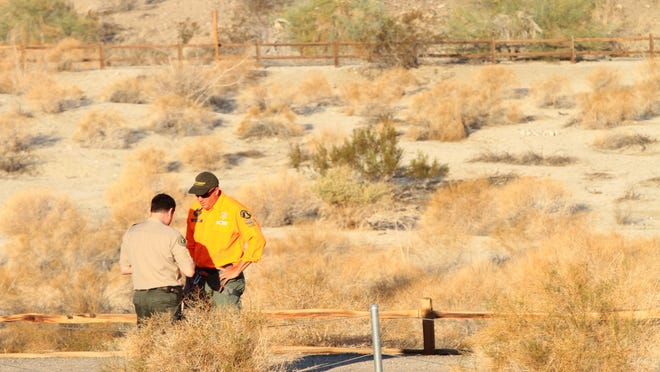 Palm Desert Police Sgt. Dave Smith and Kevin Wahlstrom of Desert Sheriff's Search & Rescue meet confer during a search.