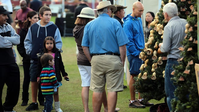 People look at Christmas trees decorated with hand sculpted ornaments made of cottonwood bark and gourds by artists Neil and Ophelia Crosier of New Mexico during Sunday's Desert Arts Festival.