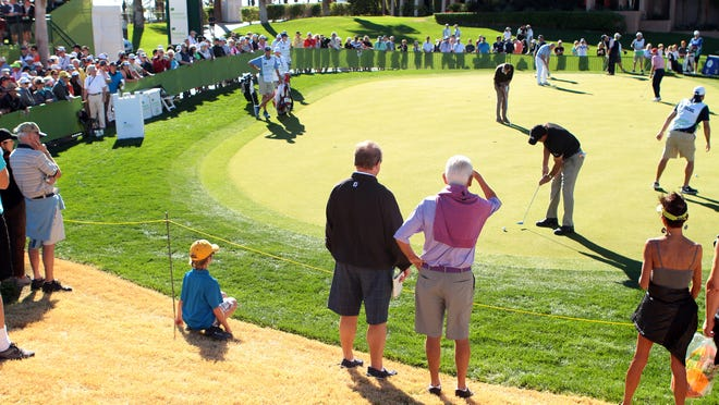 Spectators watch two-time Humana Challenge winner Phil Mickelson (at right) on the practice green before starting his round at the Palmer Private Course at PGA West during the tournament's third round on Saturday.