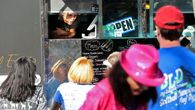 Cecelia Sanchez takes an order from the Classic Tacos window during a First Sunday's Gourmet Food Truck Fare event in Cathedral City.