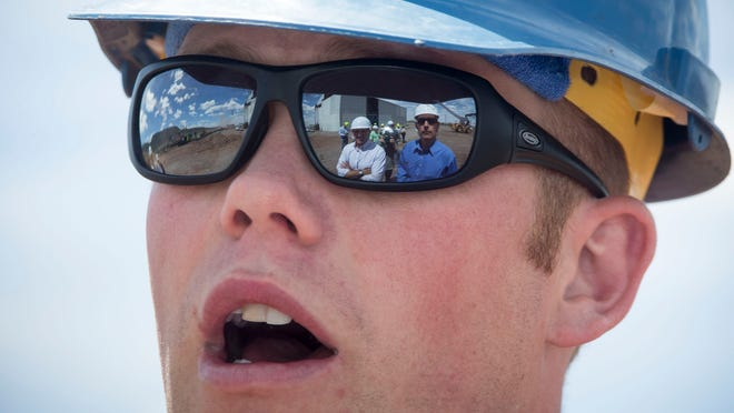 U.S. Sens. Jeff Flake (Ariz., left) and Martin Heinrich (N.M., right) are reflected in the glasses of mill manager Kurtis Vaagen at the Four Corner Forest Products mill in Eagar. Flake and Heinrich visited mills and forests April 22 for briefings on forest health.