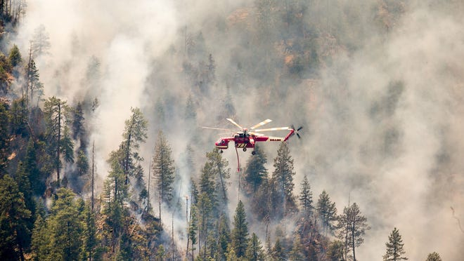Helicopters drop water on part of the Slide Fire in Sterling Canyon at the Oak Creek Overlook above Sedona on Thursday, May 22, 2014.