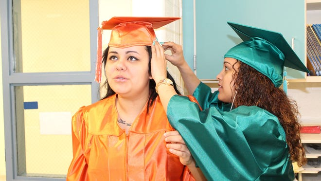 Yomarys Suarez of Kingston High School adjusts a cap for Teohva Mendoza of New Paltz High School at the graduation ceremony for students of the Ulster BOCES Center for Special and Alternative and Education.