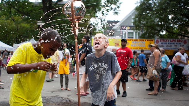 Joe Regan, right, of Rochester and Teddy Kania of Canandaigua cool off in a sprinkler during the Park Avenue Summer Arts Festival on Saturday.