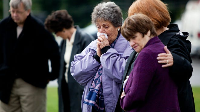 From left, Paula Krotz, Catherine Bogart and Sue Prave comfort each other as they look at pictures of the deceased.