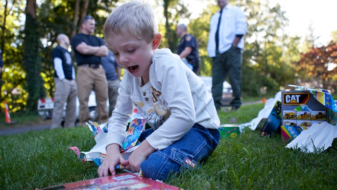 Christian Pierson opens a present delivered to him by the Rochester police tactical unit for his fifth birthday at his home on Friday.