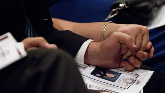 Family members of Officer Daryl Pierson hold hands during his funeral at Blue Cross Arena on Sept. 10.