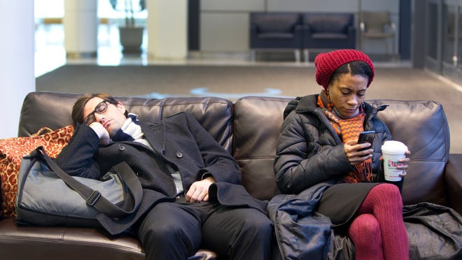 Mae Fraser of Brooklyn uses her phone as Todd Arena takes a nap while waiting for their delayed flight to New York's Kennedy International Airport at the Greater Rochester International Airport on Friday.