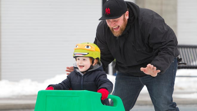 Sam Rosha of Rochester teaches his 3-year-old son, Odin, how to skate at the Dr. Martin Luther King Jr. Memorial Park at Manhattan Square.