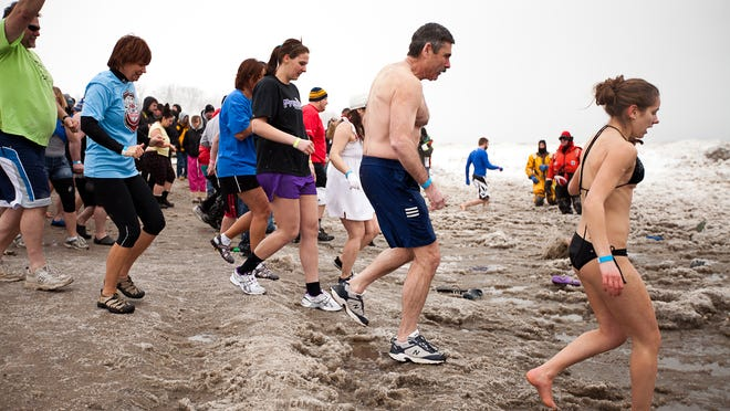 Participants of the 2012 Polar Plunge head into Lake Ontario at Ontario Beach Park to raise funds and awareness for local Special Olympics programs.
