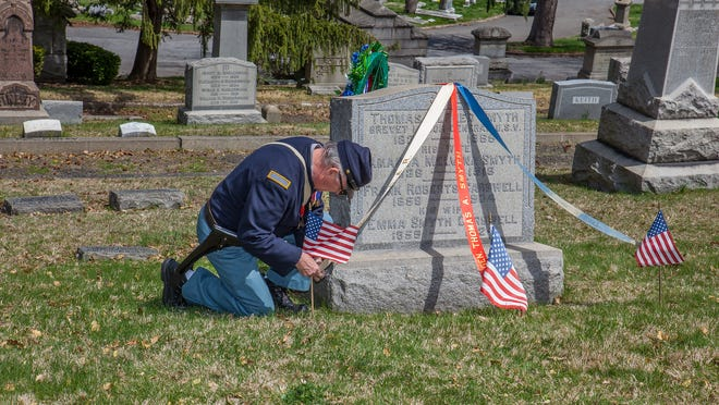 Ken Chew, secretary of The Appomattox Camp #2, secures flags and ribbons Saturday to the stone of General Thomas Smyth, the last Union general killed during the Civil War.