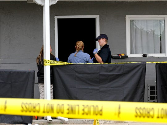 Investigators search a guest room on Sept. 14 at the Rimrock Lodge on U.S. Highway 64  in Farmington.