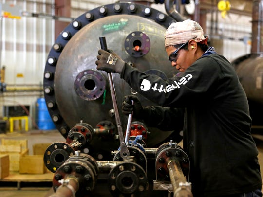 A welder tightens bolts on Friday at Process Equipment and Service Co. in Farmington.