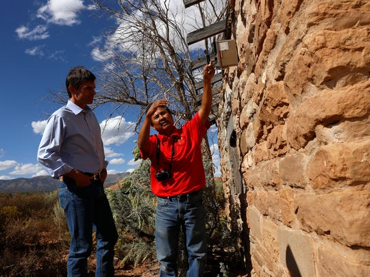Melvin H. Yazzie, senior reclamation specialist with the Navajo AML Reclamation Program, talks with U.S. Sen. Martin Heinrich as he uses a Geiger counter Friday, on an abandoned home in Oak Springs.