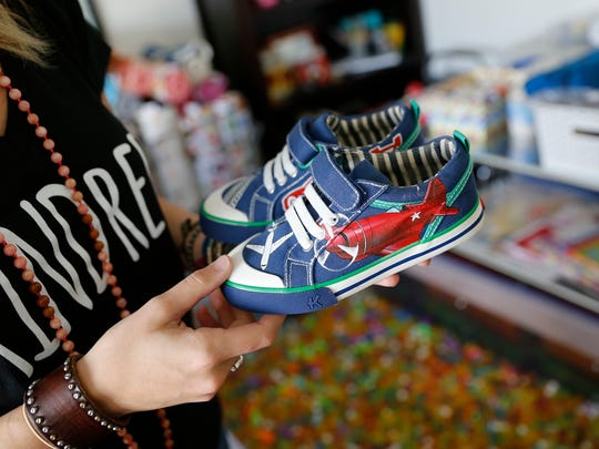 Madison Steiner shows off some of her newly designed shoes Saturday during an open house event for The Mad Lab in Farmington.