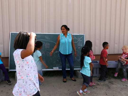Teacher Tonniale Clichee works with her students on Wednesday at Dream Diné Charter School in Shiprock.