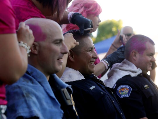 Farmington Police Lt. Donnie Kee, center, has his hair