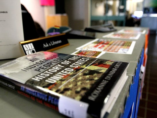 Books, fliers and posters about Indigenous Peoples' Day are displayed at a booth on Monday at San Juan College in Farmington.