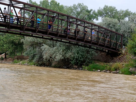 People look down at the Animas River from a bridge at Berg Park in Farmington on Aug. 8 as a plume of toxic wastewater from the Gold King Mine spill passes through the city.