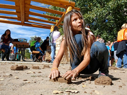 Fourth-grader Nevaeh Wolfe, 10, molds an adobe brick