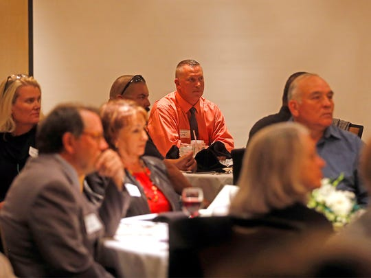 Audience members listen as Sheryl Clark speaks Thursday at the Courtyard by Marriott in Farmington.