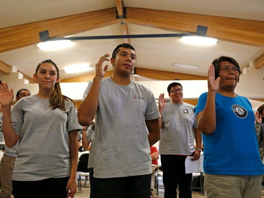 Emily Hunt, left, Rashaun Nez and Lisajann Begay stand for the AmeriCorps Pledge on Friday during a ceremony at the Nenahnezad Chapter House.