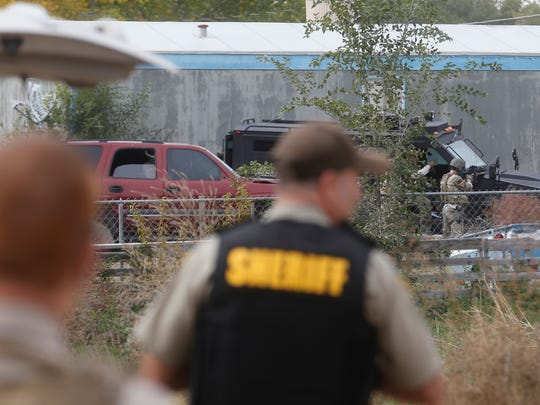 Members of the Farmington police SWAT team surround a home Wednesday in the Lee Acres subdivision east of Farmington.