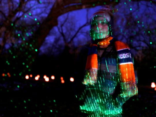 Children run through an area lit with green lights on Dec. 5 during RiverGlo at Berg Park in Farmington.