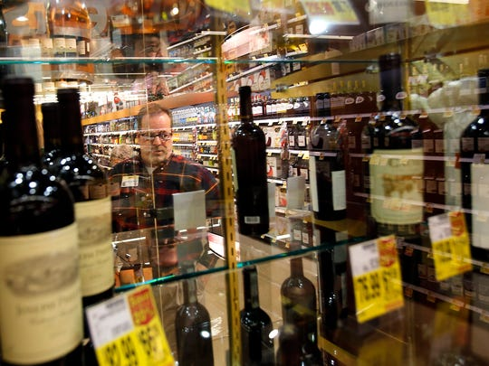 Store director Brian Van Klavern talks Friday about the high-end alcohol now offered at Smith's Food and Drug in Farmington.
