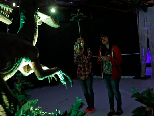 Tahleiah Begay, left, and her cousin Temiah Begay examine a dinosaur display Saturday at the McGee Park Convention Center.