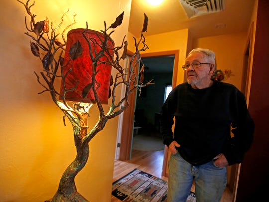 Don Hammontree, 75, of Aztec, shows off a few of his sculptures inside his home on Wednesday.