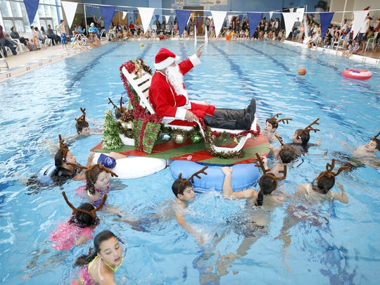 Children pull Santa around the pool during a Christmas celebration at the Bloomfield Family Aquatic Center on Dec. 13.