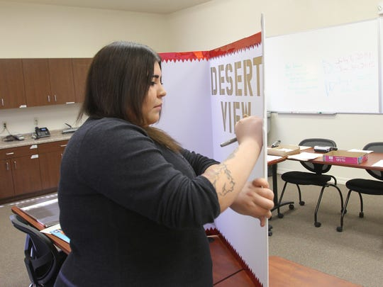 Administrative assistant Mariana Medran on Tuesday works on a poster board for Desert Family Counseling's upcoming grand opening in Farmington.
