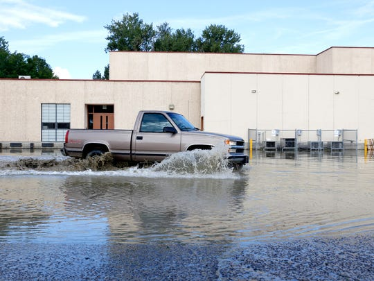 A vehicle drives through a heavily flooded parking lot on the back side of Aztec High School on Aug. 27.