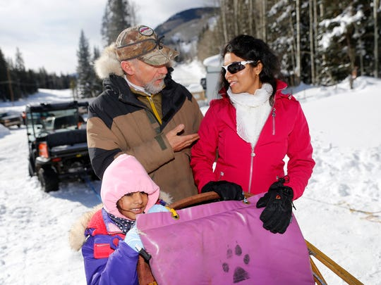 At center, Durango Dog Ranch owner and operator Gregg Dubit teaches Ridhi Danduprolu, left, and her mother, Siri Koppanati, how to turn a dog sled on Tuesday at the Purgatory Resort kennel north of Durango, Colo.