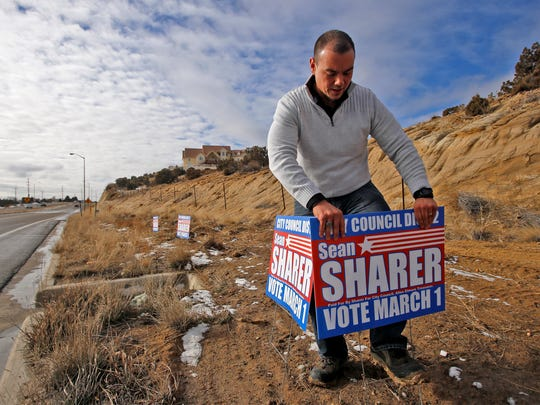 Sean Sharer, a candidate for Farmington City Council,  puts up campaign signs on Tuesday along Piñon Hills Boulevard in Farmington.