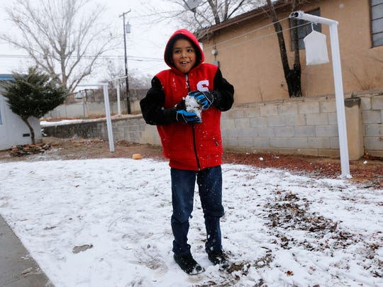 Demetrius Sandoval prepares a snowball to throw at his sister on Friday on North Wall Avenue in Farmington.