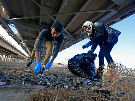 From left, AmeriCorps members Alejandro Cota and Shaneyka Yazzie pick up trash on Monday next to Nizhoni Park in Shiprock.